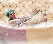 Bizarre ugly man washing his leg in a bath
