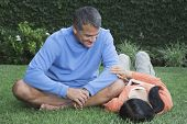 Hispanic couple relaxing in grass