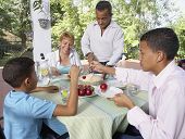 Hispanic family eating pie outdoors