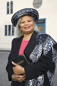 stock photo of piety  - Senior African American woman in front of church - JPG