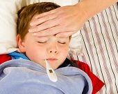 Sick child boy being checked for fever and illness while resting in bed