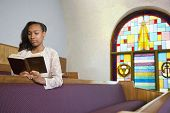 image of pews  - African American woman reading Bible in church - JPG
