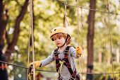 Kids Boy Adventure And Travel. Cute School Child Boy Enjoying A Sunny Day In A Climbing Adventure Ac poster