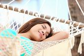 Vacation woman lying in hammock relaxing and sleeping smiling happy during summer holidays in tropic