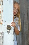girl peeking around old door
