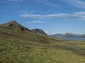 Beautiful Landscape Of Blue Alftavatn Lake And River With Snow Covered Mountains And Green Hills And poster