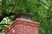 stock photo of chimney  - aluminum chimney cap on top of brick chimney - JPG