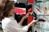 Young Woman Holding Black Heeled Shoe And Red Defocused Heeled Shoe In Shop. Photo With Depth Of Fie poster