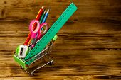 Buying School Supplies. Shopping Cart With School Supplies On A Wooden Background. Back To School Co poster