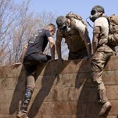 POCONO MANOR, PA - APR 29: A man pulls himself up and over the Berlin Walls obstacle at Tough Mudder