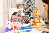 Kids With Teacher Make Hands Crafts In Kindergarten. Children Prepare To Christmas In Daycare. Group poster