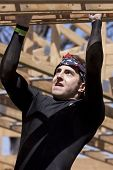 POCONO MANOR, PA - APR 29: A man moves hand-over-hand through an obstacle at Tough Mudder on April 29, 2012 in Pocono Manor, Pennsylvania. The course is designed by British Royal troops.