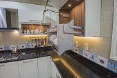 Interior Design Decor Showing Modern Kitchen With Swinging Cupboard In Luxury Apartment Showroom poster