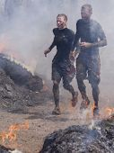 POCONO MANOR, PA - APR 28: A couple runs through the Fire Walker obstacle at Tough Mudder on April 28, 2012 in Pocono Manor, Pennsylvania. The course is designed by British Royal troops.