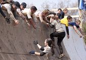 POCONO MANOR, PA - APR 28: Men help other participants up the Everest obstacle at Tough Mudder on April 28, 2012 in Pocono Manor, PA. The course is designed by British Special Forces.