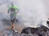 POCONO MANOR, PA - APR 28: A man runs through the Fire Walker obstacle at Tough Mudder on April 28,