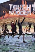 POCONO MANOR, PA - APR 29: Participants move hand-over-hand through an obstacle at Tough Mudder on A