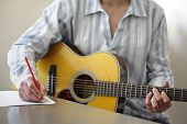 stock photo of guitarists  - Guitarist musician writing a song on his guitar - JPG