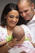 stock photo of snuggle  - Happy Young Attractive Mixed Race Family with Newborn Baby - JPG