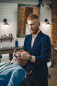 Barber Shop Studios. Barber Shaving A Bearded Man In A Barber Shop. Beard Man Visiting Hairstylist I poster