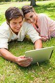 lächelnd gegen ihre Freundin lehnt sich, wie sie eine Tablette zusammen verwenden, während auf dem Rasen liegend