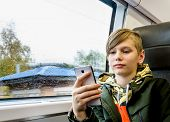 Teenager Sitting Near The Window And Using His Smartphone While Traveling By Train poster