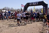 POCONO MANOR, PA - APR 29: Participants run across the starting line at Tough Mudder on April 29, 2012 in Pocono Manor, Pennsylvania. The course is designed by British Royal troops.