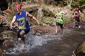 POCONO MANOR, PA - APR 28: Participants run through a flowing cold water creek at Tough Mudder on Ap