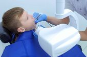 Making X-ray Of Teeth For Teenage Boy In Dentistry Clinic, Side View. Dentist Scaning Jaw On X-ray F poster
