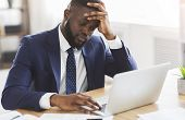 Professional Crisis. Depressed African Guy In Formal Suit Sitting In Front Of Laptop At Workplace, C poster