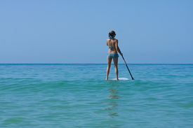 stock photo of stand up  - Woman standing on a Stand up paddleboard in the ocean - JPG
