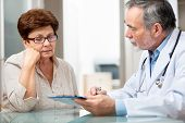 stock photo of visitation  - doctor talking to his female patient at office - JPG