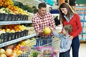 woman with man and child choosing melon fruit during shopping at vegetable supermarket