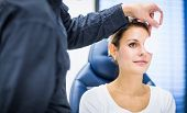 Optometry concept - pretty young woman having her eyes examined by an eye doctor/optometrist (color