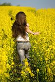 Girl running in the blooming rapeseed field