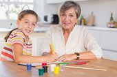 Child with her grandmother looking at the camera while drawing in kitchen