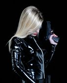 stock photo of pistol  - Young blonde woman with black dress holding a gun - JPG