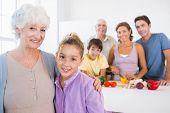 Großmutter und Enkelin stehen neben Zähler mit Familie dahinter