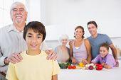 Großvater und Enkel, die neben der Küchentheke mit Familie dahinter stehend