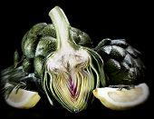 stock photo of artichoke hearts  - Thre artichoke heart with lemons and herbs - JPG