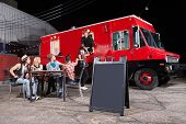 stock photo of canteen  - Happy diners at food truck with blank sign - JPG