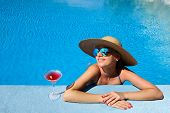 stock photo of cosmopolitan  - Woman in hat relaxing at the pool with cosmopolitan cocktail - JPG