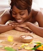 Photo of attractive african woman on massage table in luxury spa salon, smiling female enjoying spa