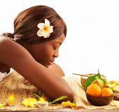 Photo of lovely African woman with closed eyes and white franjipani flower in head relaxed on massag