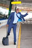 funny african american businessman calling taxi at airport