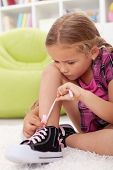 Little girl ties shoes with great care and concentration