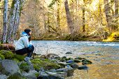 picture of mckenzie  - A female hiker takes a rest and looks out over the water of the McKenzie River in Oregon - JPG