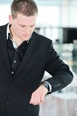 stock photo of wind up clock  - Businessman looking at clock wristwatch on hand in office - JPG