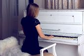 girl with blond long hair in dress playing white piano