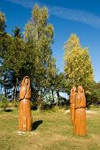 Wooden sculptures in the meadow in front of trees